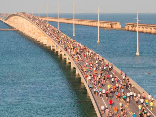 In this aerial photo provided by the Florida Keys News Bureau, a portion of a field of about 1,500 runners reaches the top of the Florida Keys Overseas Highway's longest bridge during the Seven Mile Bridge Run Saturday, April 14, 2018, near Marathon, Florida.  The race over the convergence of the Atlantic Ocean and Gulf of Mexico was initiated in 1982 to mark the completion of a federally funded bridge rebuilding program to replace 37 aging spans originally built in the early 1900s to carry railroad trains.