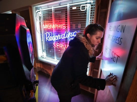 """After the official cake-cutting ceremony at Graceland to celebrate Elvis' 83rd birthday, Archives Manager Danielle Forbes puts a few finishing touches on a new exhibit, """"Hollywood Backlot,"""" before a ribbon cutting ceremony. The exhibit features sets and items from the production of the short-lived 2017 CMT Network series """"Sun Records."""""""