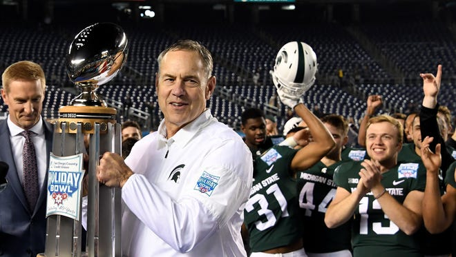 Mark Dantonio smiles with the bowl trophy as his team cheers on after MSU beat Washington State, 42-17, in the Holiday Bowl.