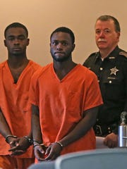Larry Taylor, from left, and Jalen Watson are escorted