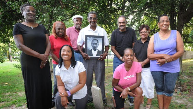 """The Rev. Lucille Nichols of Scott's United Methodist Church in Trappe joins descendants of Nathaniel """"Uncle Nace"""" Hopkins behind the church where the first Hopkins tombstone, and that of his wife, Caroline, were placed in the 1970s. With Nichols, from left, are Violece Brown, Robert Chase, his brothers Walter and Joe, Jacki Gibbs and Joyce White. Front, from left, are Nichole Chase-Powell and her sister, Robin Chase. Walter Chase holds a photo of Nace Hopkins, who was a political activist and civic leader in Trappe and originator of the annual Emancipation Day Parade and program. Hopkins died in 1900."""
