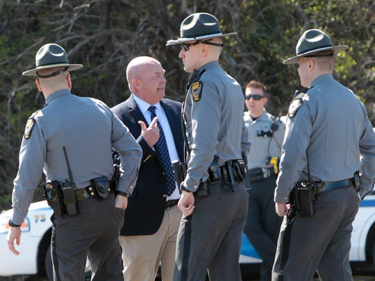 Major Mike Horton (second from left), of the Hamilton County Sheriff's department, briefs three Ohio State Troopers after they arrived at the scene on southbound I-75,  just south of Sharon Road.