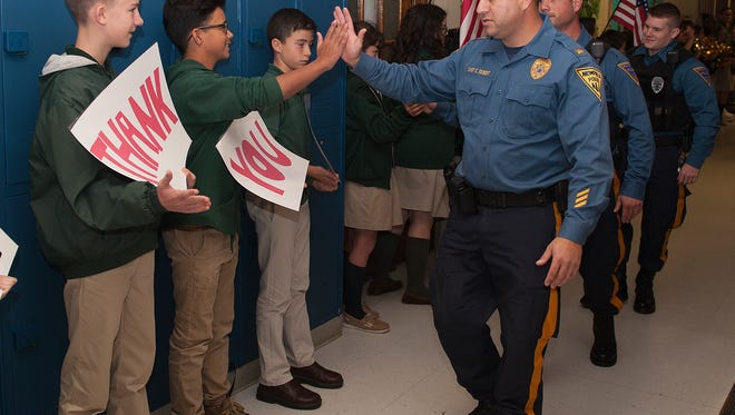 Newfield Police Chief, Edward Seibert, high fives student Jordan Baez during the luck gauntlet walk, Tuesday, Oct. 17, 2017, with students from Edgarton Christian Academy. Students honored Newfield Police, which apparently disband on Nov. 1.