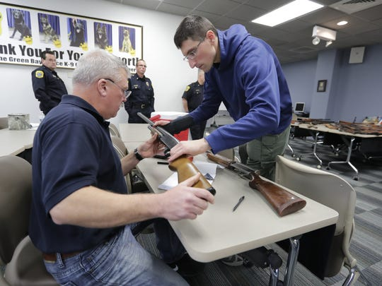 Green Bay Police officers Bob Matheny, left, and Tom Behn catalog and trace the dozens of guns surrendered to the department during its gun buyback program. The program netted nearly 100 guns Saturday.
