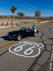 A woman poses with a car along route 66 in Needles, California.