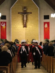 The Knights of Columbus march in step down the aisle