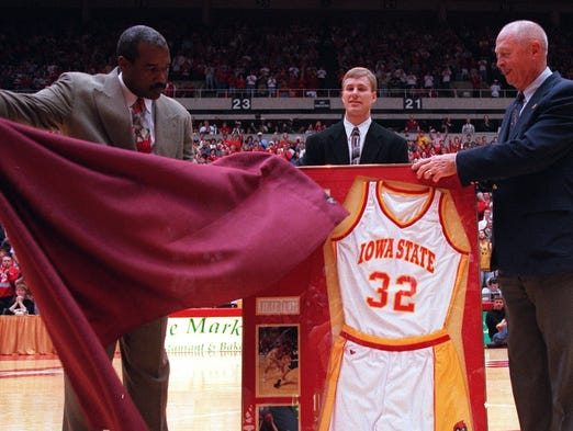 ISU athletic director Gene Smith sweeps cover away from Former ISU staar Fred Hoiberg's number, Hoiberg at center, which was retired at halftime of KU game. Former ISU coach Johnny Orr at right.