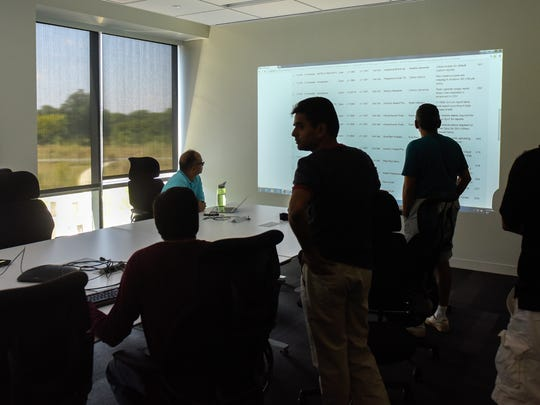 Commvault employees go over a slide presentation at