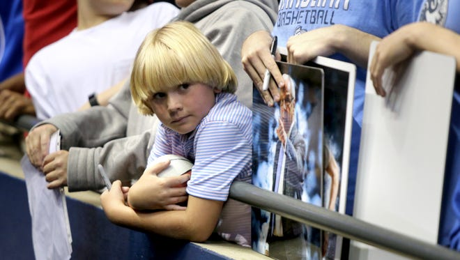 Basketball fan Hamilton Eggers, 8, waits for autographs during the NCAA South Regional open practice Thursday.