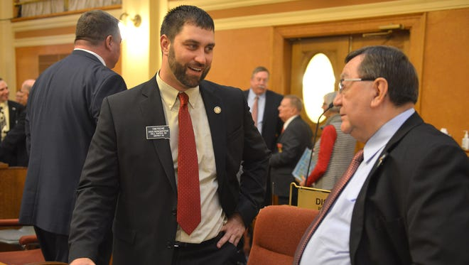 Reps. Tom Pischke, left, and Larry Zikmund talk after the State of the State address Tuesday in Pierre.