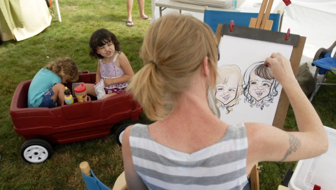 Two girls sit patiently in a wagon as Jenny Powers, of Ferndale, draws their caricatures during a previous Algonac Art Fair.