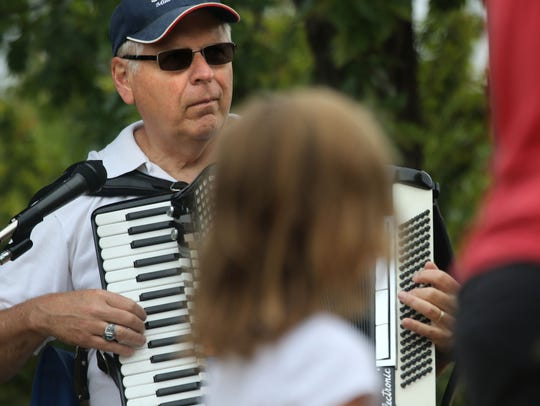 Marv Wunder plays his accordion for shoppers at the
