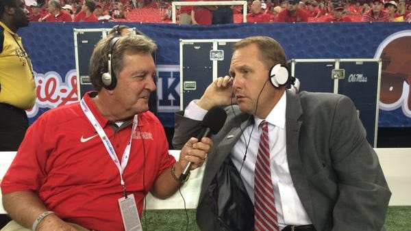 Longtime Ole Miss sideline reporter Stan Sandroni talks to coach Hugh Freeze before this year's season opener. Sandroni died Wednesday at the age of 64.