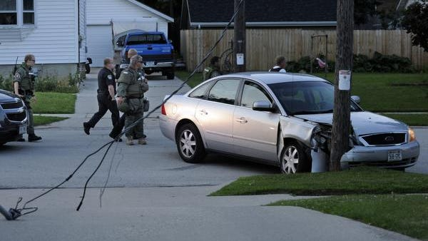 Manitowoc Police, Sheriffs officers, and SWAT members search for the driver of a silver Ford which evaded a police stop and crashed into a telephone pole on Clark Street between South 22nd and South 23rd Streets on Thursday, July 10, 2014 in Manitowoc. Power lines fell and were sparking until Manitowoc Public Utilities shut off power. The driver ran after the collision and one woman is in custody.