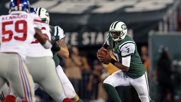 Jets quarterback Geno Smith scrambles during the first quarter against the Giants at MetLife Stadium on Friday night.