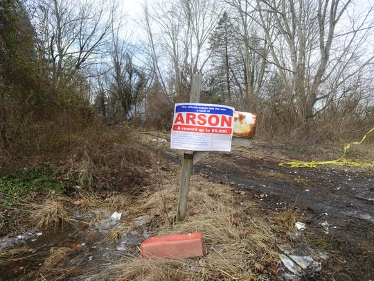 A sign asking for imformation about an arson fire hangs from a battered mailbox in front of a vacant house on Newark Road in Nashport that burned early Tuesday morning.