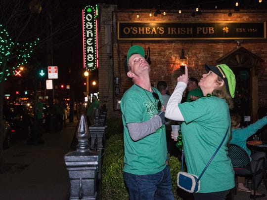 "Kevin Sewell and Judi Eldridge have drinks in the garden at O'Shea's Irish Pub and notice that someone ""rolled"" the trees as others watch the Indiana vs. Chattanooga NCAA game on a large sceen television outside during St. Patrick's Day festivities. March 17, 2016"