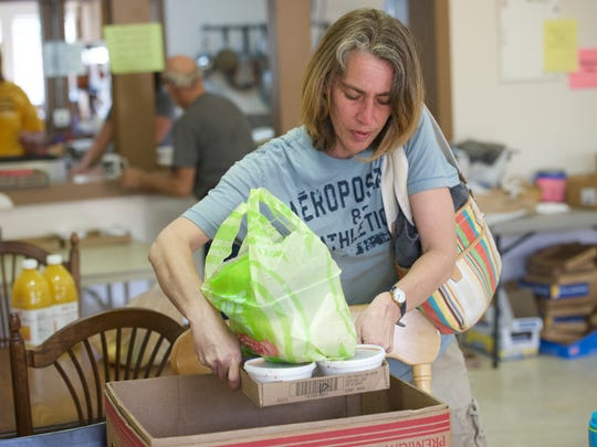 Meredith Bradshaw boxes up food from the Morgan County Starting Points.