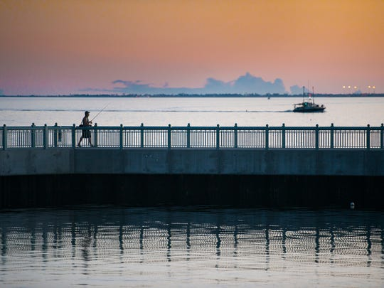 Ryan Deen fishes from the pier as the sun sets at Maritime