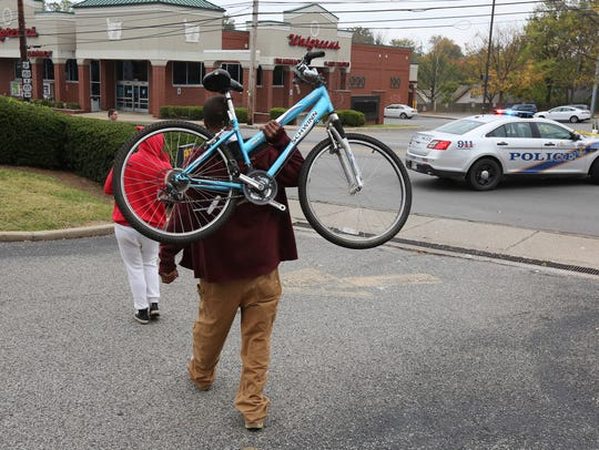 Chris Morris carries his damaged bike away from the