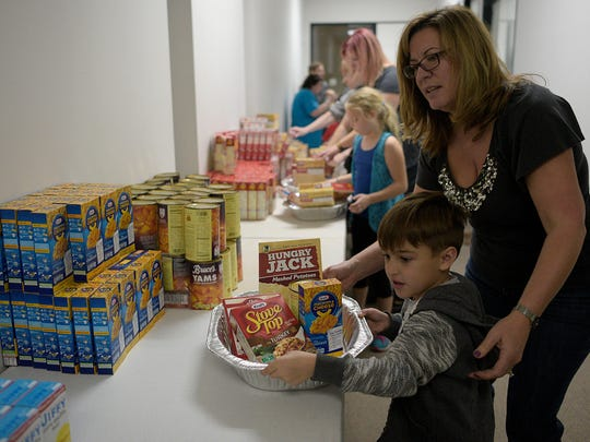 Dominic Freda, 6, and his mother Julie prepare a Thanksgiving basket.   JUNFU HAN   STAFF PHOTOGRAPHER