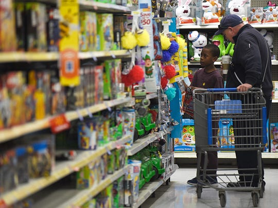 Kelly Blade of Lyon Township firefighter helps Kenneth McKennedy, 10, pick out a toy.   JUNFU HAN | STAFF PHOTOGRAPHER