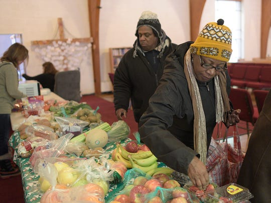 Betty Euseary picks out fruits and vegetable for her family at the Redford Brightmoor Initiative.