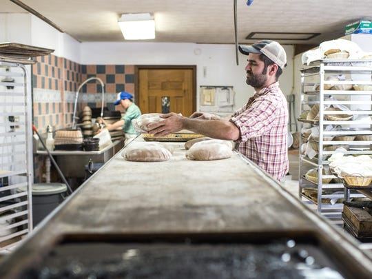 Head baker and owner David Bauer places loaves on a rack to be put in a brick oven, Friday, April 17, 2015.