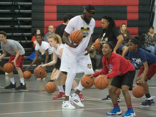 Former NBA player, Reggie Evans, center, teaches middle and high school students a variety of ball handling skill and footwork drills during a basketball clinic at West Florida Baptist Church Monday, Feb. 20, 2017.
