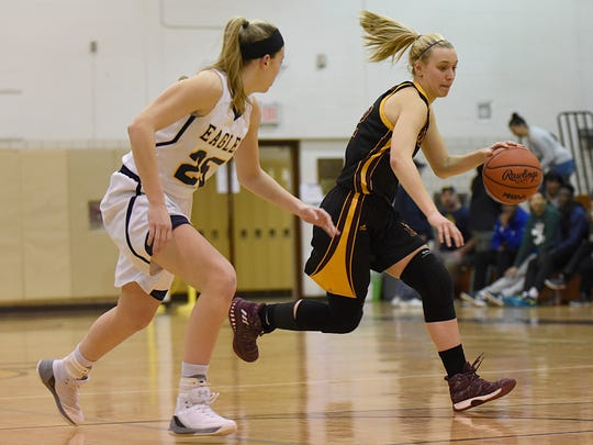 Mercy's Jenna Schluter (right) dribbles by Hartland defender Lexey Tobel.