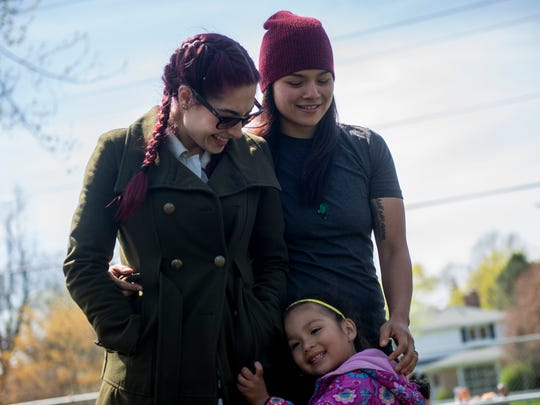 MMA fighter Aurelia Cisneros, right, and her fiancee Alison Wilson stand together as Cisneros' daughter Lilyana hugs both of them on Saturday, April 22, 2017 at Patriarche Park in East Lansing during Lilyana's birthday party. She turned 4.