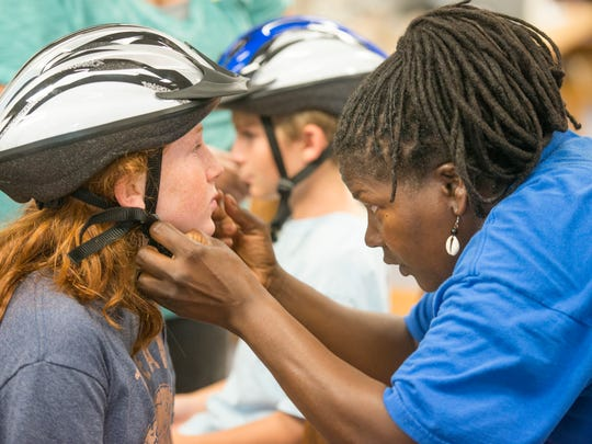 Zakkiyyah Osuigwe, a volunteer with Escambia-Santa Rosa Community Traffic Safety Team, helps fifth grader Bella Maltese adjust her new bike helmet at Hellen Caro Elementary School in Pensacola on Tuesday, May 23, 2017.