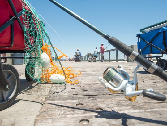 People fish off the pier in Navarre Beach on Thursday,