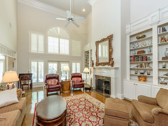 The living room areas feature soaring ceilings with