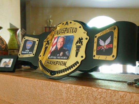 A championship belt for Officer Vega sits on the mantle of his son Isaac Vega's home, September 24, 2017.