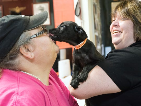 "Mia Burke, left, share kisses with ""Annona,"" a mixed-breed"