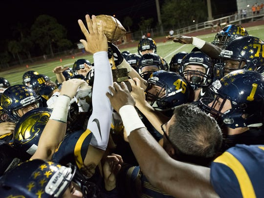 Naples players celebrate winning the Joe Klimas Trophy, known as 'The Nut,' after beating Lely 42-7 to win the Coconut Bowl at Naples High last year.