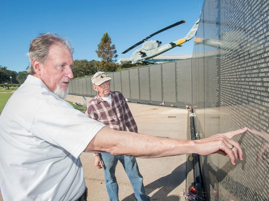 Navy Vietnam War veteran , right, looks on as Marine Corps Vietnam War veteran Lenny Collins looks for the name of a friend on Wall South at Veterans Memorial Park in Pensacola on Tuesday, October 24, 2017.  A plaque, which recognizes these men and the others who helped make the park and  Wall South a reality, will be unveiled during a ceremony commemorating its 25th anniversary this year on Veterans Day.