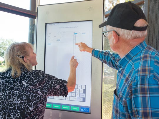 Navy veteran and park volunteer Warren Palmer, right,  helps Gloria Collins search for the location of a friend's name on Wall South at Veterans Memorial Park in Pensacola on Tuesday, October 24, 2017.  A plaque, which recognizes Collins' husband Lenny and the others who helped make the park and Wall South a reality, will be unveiled during a ceremony commemorating its 25th anniversary this year on Veterans Day.