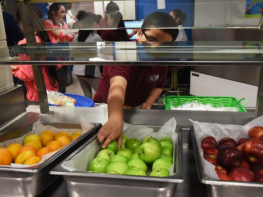 A partnership between Sara Elnakib of Rutgers Cooperative Extension of Passaic County and David Buchholtz the Director of food services at Paterson Public Schools lead to a reduction in food waste by allowing children to select from a wide array of healthy fruits and vegetables. Shown at Charles Riley School #9 on Thursday June 07, 2018. A young student reaches for an apple during lunch.