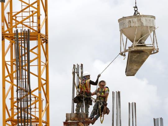 Construction workers pour concrete Wednesday on one of multiple new buildings, including new restaurants, going up near the Gulf Coast Town Center on Alico Road.