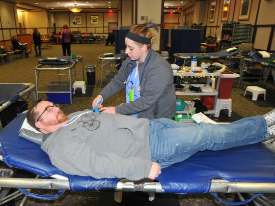 Holly Sullivan prepares Tony Foster for his blood donation Saturday during the Baby Tressel Day blood drive at Reid Health.