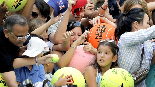 In this Aug. 31, 2019, file photo, tennis fans crowd the edge of the court hoping for an autograph from Rafael Nadal during the third round of the U.S. Open tennis championships in New York.