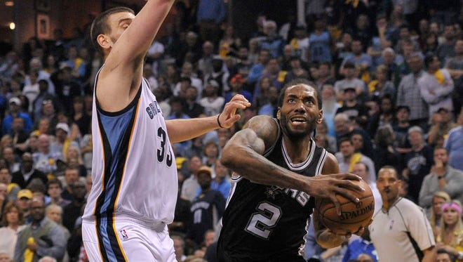 San Antonio Spurs forward Kawhi Leonard goes to the basket against Memphis Grizzlies center Marc Gasol during the second half in game four of the first round of the 2017 NBA Playoffs.