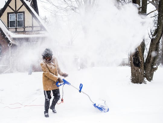 Wind pushes snow back onto Sarah Allen as she clears
