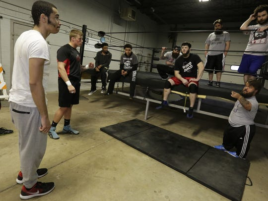 Dylan Postl, bottom right, speaks to a group of wrestlers