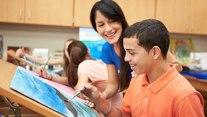 Male Pupil In High School Art Class With Teacher
