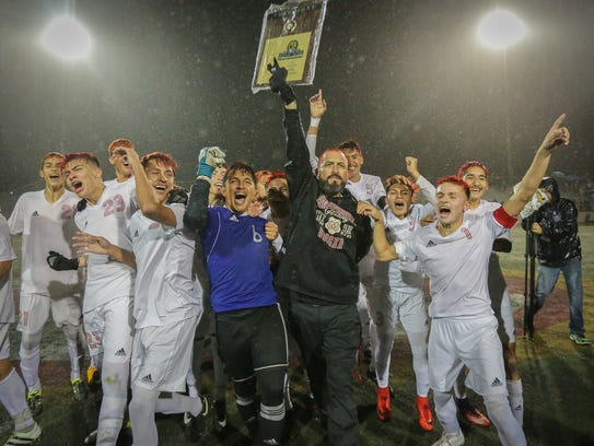 The Desert Mirage High School boys' soccer team raises the championship trophy in celebration after scoring a late goal to edge Indian Springs of San Bernardino 3-2 in the CIF-SS Division 4 championship game. Photo by Brandon Magpantay/Special to The Desert Sun