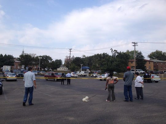 Onlookers surround the shooting scene, where many of their cars are parked.