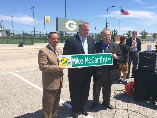 Green Bay Packers coach Mike McCarthy, center, poses with Green Bay Mayor Jim Schmitt, left, and Ashwaubenon Village President Mike Aubinger after receiving a Mike McCarthy Way street sign on Wednesday.